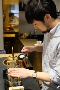 Barista preparing a pour over via nel drip and copper kettle at Cobi Coffee Aoyama Tokyo Japan