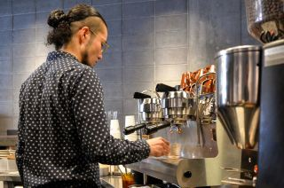 Barista prepares espresso at The Roaster by Nozy Coffee Jingumae Tokyo Japan