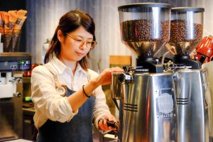 Barista Grinding Coffee at The Roaster by Nozy Coffee Jingumae Tokyo Japan