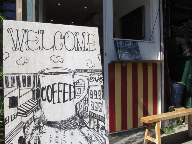 Welcome Coffee Sign with Cafe in distance Woodberry Coffee Roasters in Yoga Tokyo Japan