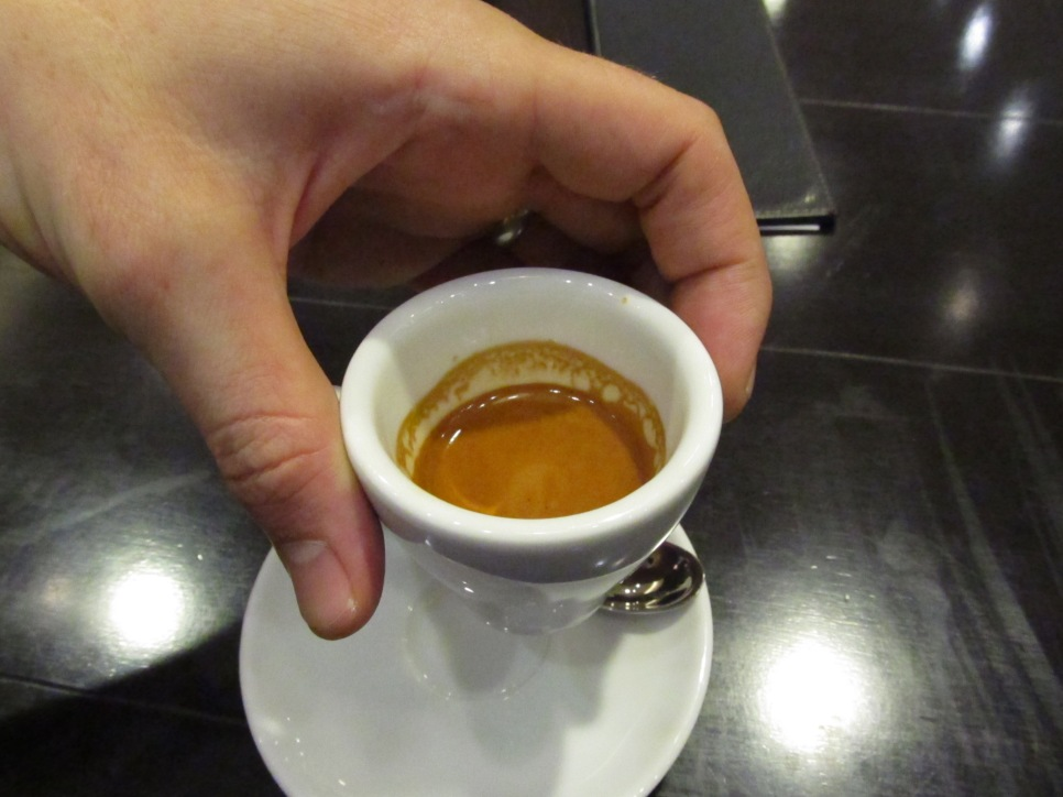 An espresso cup and saucer in hand at Paul Bassett Coffe Shibuya Tokyo Japan