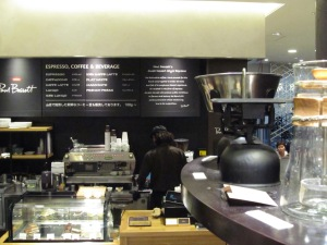 Coffee Items on a Shelf in foreground Barista on espresso machine in background at Paul Bassett Coffee Shibuya Tokyo Japan