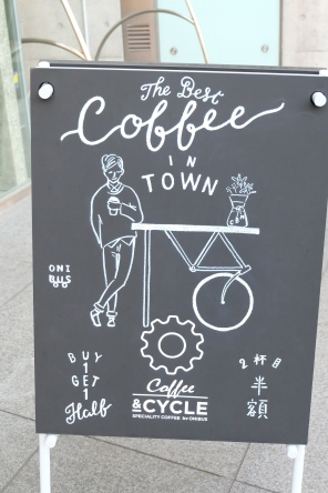 The Best Coffee in Town Buy 1 Get 1 Half Coffee and Cycle sign outside of Ratio Coffee & Cycle