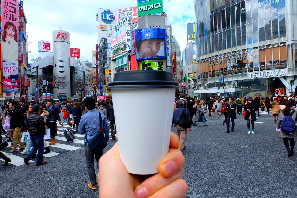 Coffee Cup being held in hand at Shibuya Crossing Tokyo Japan