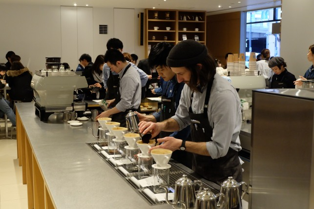 Barista preparing a pour over at Blue Bottle Coffee Shinjuku Tokyo Japan