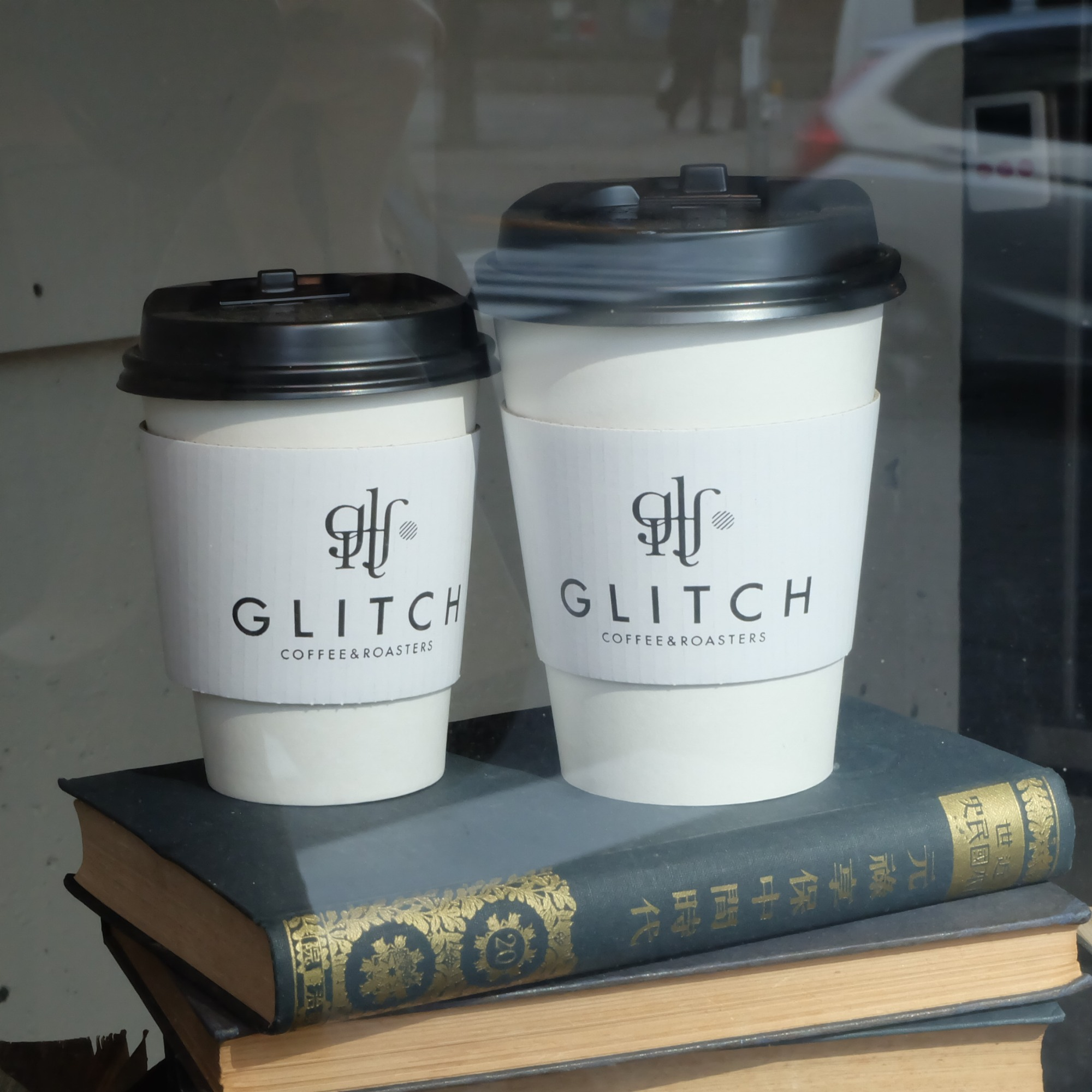 Paper coffee cups on Japanese book at Glitch Coffee and Roasters in Jimbocho Tokyo Japan
