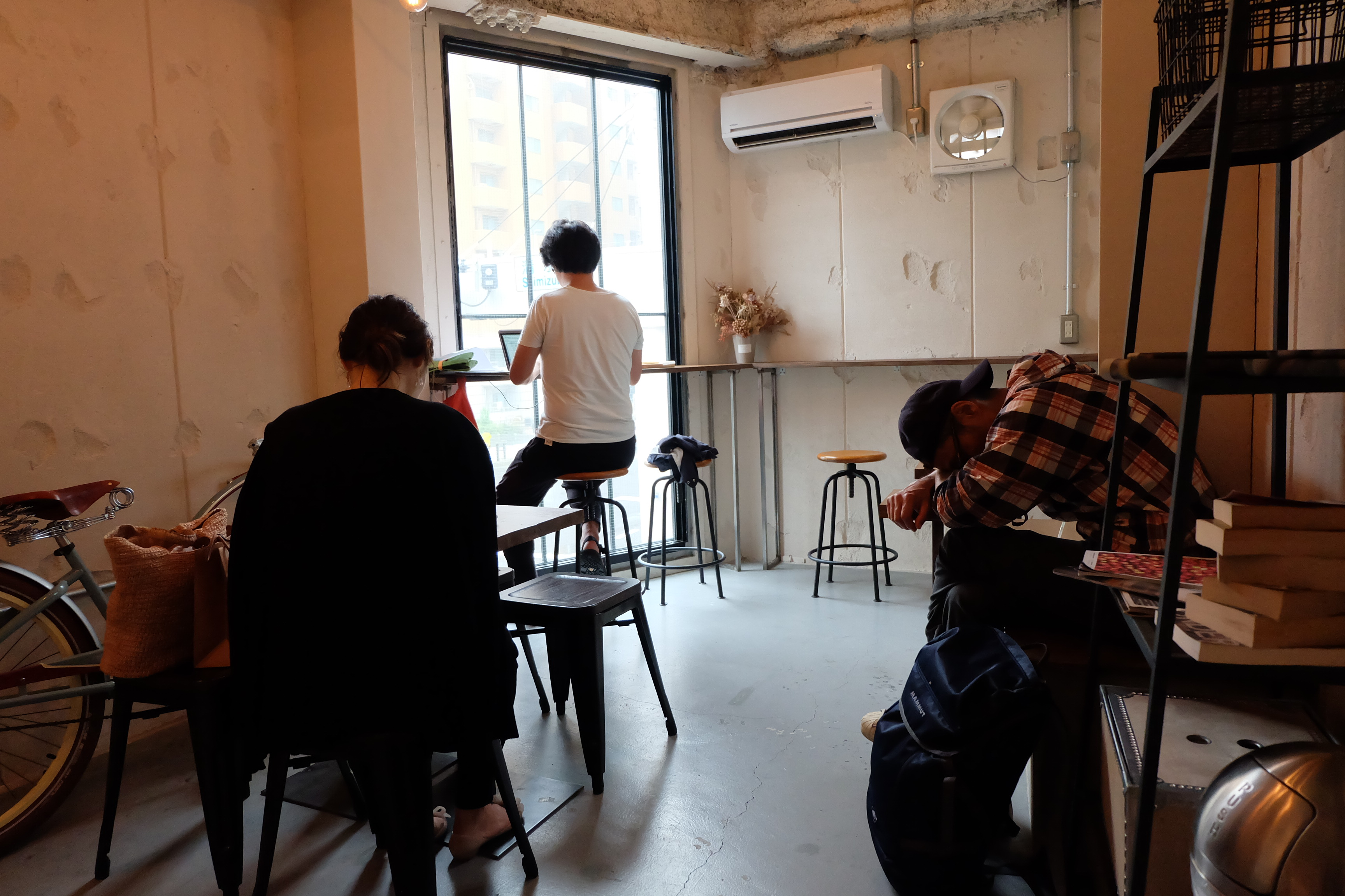 Customers working and sleeping at Counterpart Coffee Gallery Nishi Shinjuku Tokyo Japan