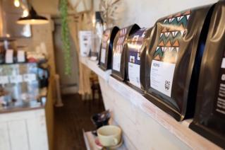 Coffee bags lined on a shelf at Onibus Coffee Okusawa Tokyo Japan