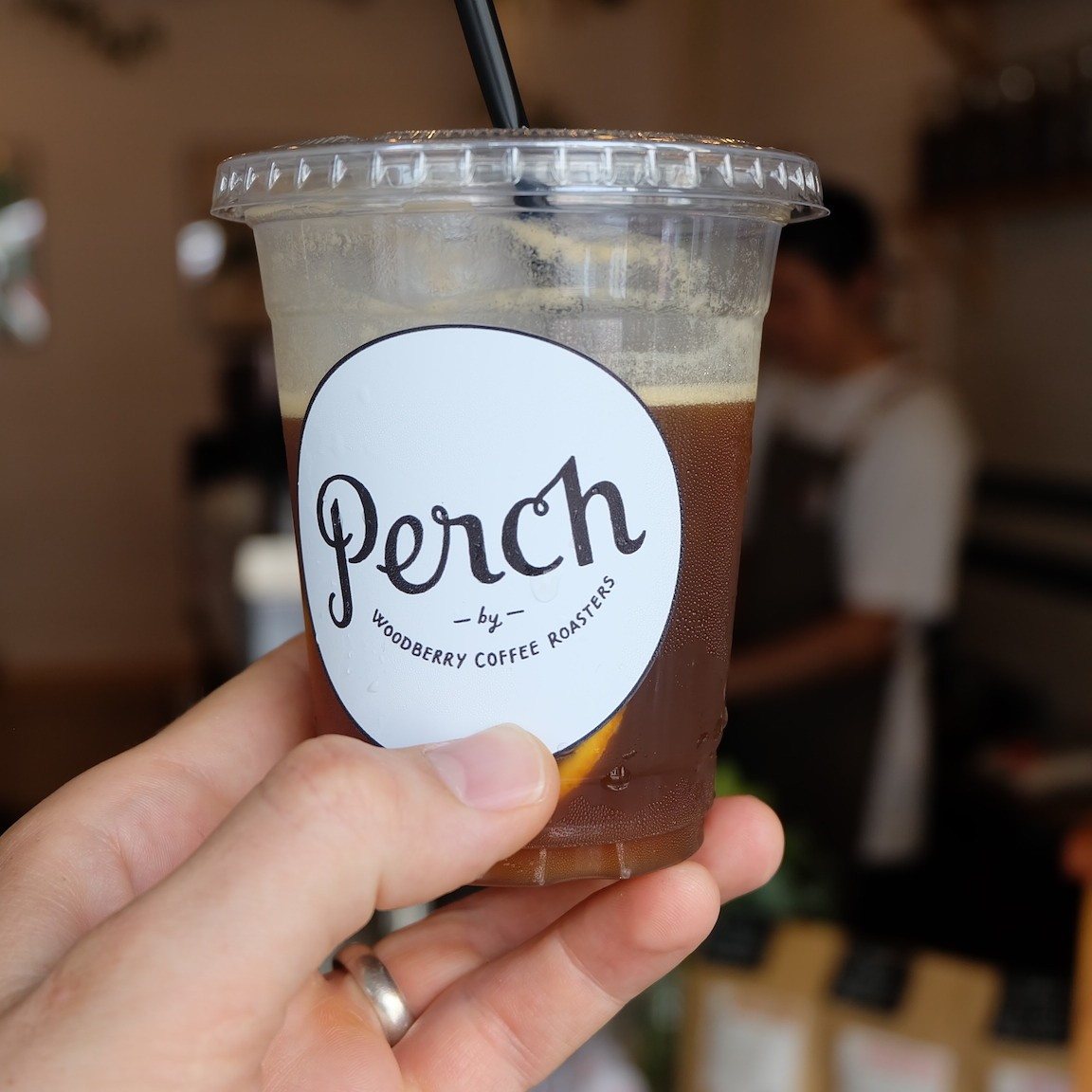 Hand Holding Iced to-go cup at Perch by Woodberry Coffee Roasters Tokyo Japan