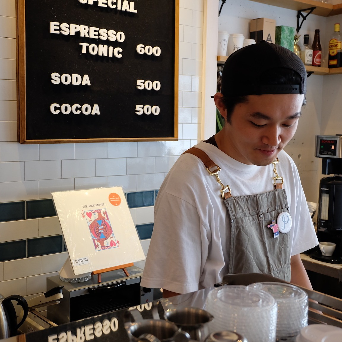 Barista looks over espresso machine at Perch by Woodberry Coffee Roasters Tokyo Japan