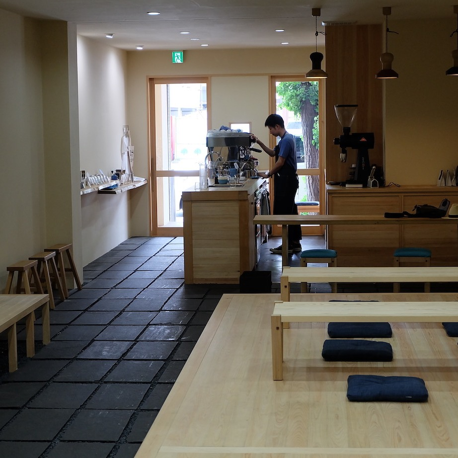 Barista at Light Up Coffee Kyoto working by window