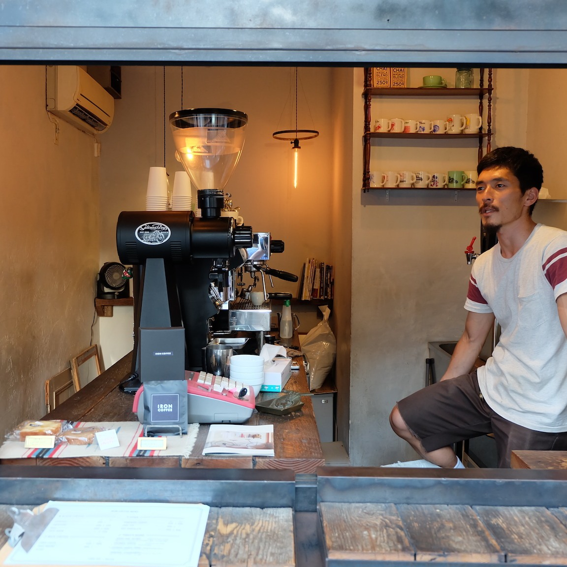 Barista sits on counter at Iron Coffee at Gotokuji Tokyo Japan